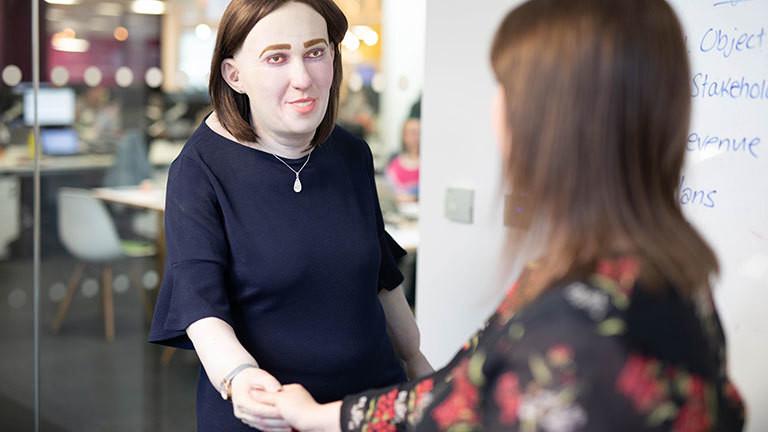 Eine Wachspuppe im Büro mit geröteten Augen und einem Buckel.