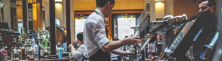 Ein Barkeeper steht hinter der Theke und zapft ein Bier
