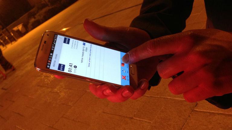 Ein Mann zeigt auf einem Smartphone eine App.