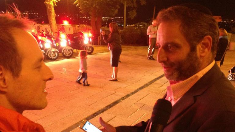 Ein Reporter interviewt einen Mann mit Smartphone in der Hand.