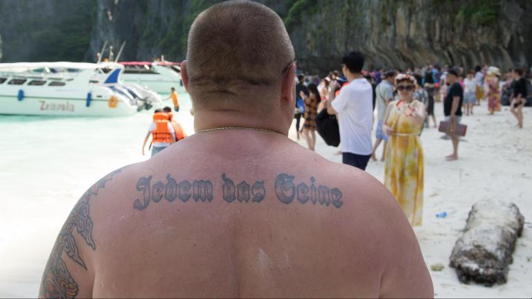 """Neo-Nazi Neo-Nazi mit Tattoo """"Jedem das Seine"""" steht am Strand von Maya Bay auf Ko Phi Phi Leh, Thailand, aufgenommen am 23.07.2017."""
