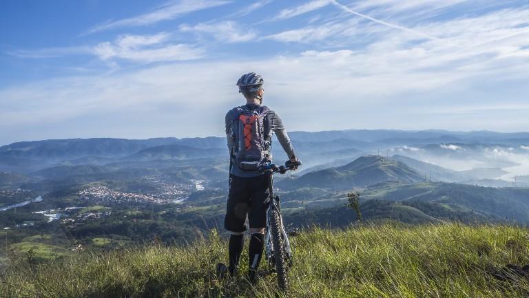 Ein Mann steht mit seinem Rad auf dem Berg und schaut auf ein Tal