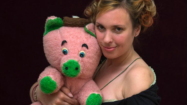 Frau mit einem rosa Plüschschwein im Arm.