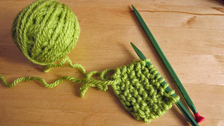 Ein grüner Topflappen wird gestrickt.