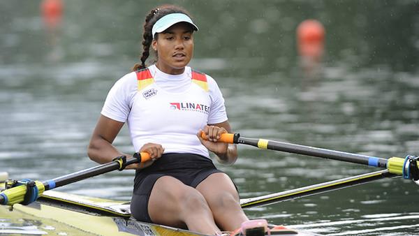 Eine Frau sitzt in einem Ruderboot und trägt eine weiße Cappy.