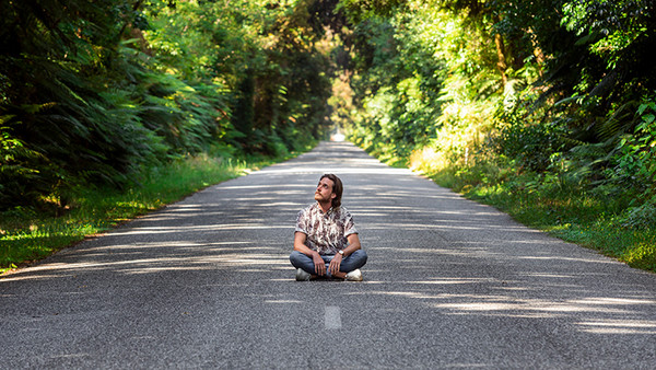 Ein Mann sitzt im Schneidersitz auf einer Straße, rundherum ist Wald.