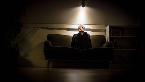 Eine Frau sitzt auf einem Sofa und hält sich die Augen zu, an der Wand hängt ein Licht, das sie anstrahlt.