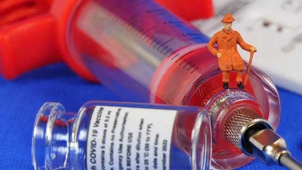 Symbolbild: Auf einer Corona-Impfstoffdose mit Spritze sitzt ein Senior