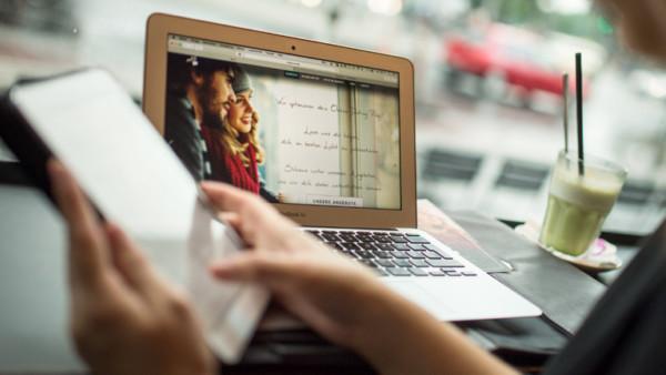 Zwei Hände halten ein iPad. Dahinter steht ein Laptop auf dem eine Dating-Seite zu sehen ist.