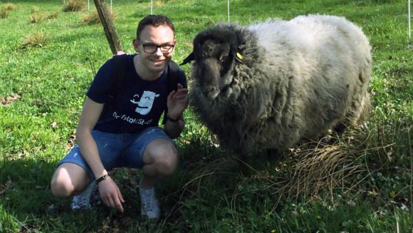 Tim Hartmann kniet neben einem Schaf