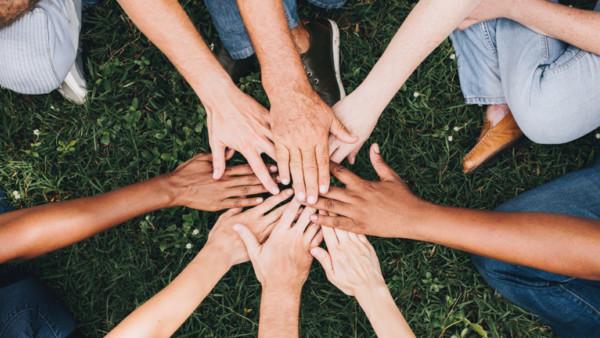 Acht Menschen legen ihre Hände übereinander