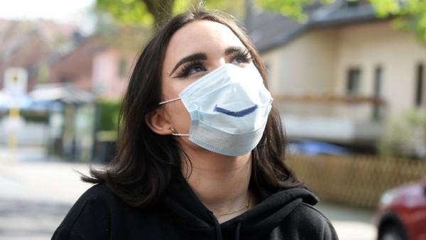 Eine junge Frau mit Maske und einem lächelnden Mundwinkel darauf