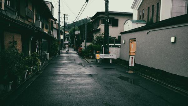 Eine Frau läuft durch eine leere Straße in Kyoto