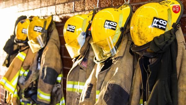 In einer Reihe sind gelbe Helme und Schutzanzüge aufgehängt