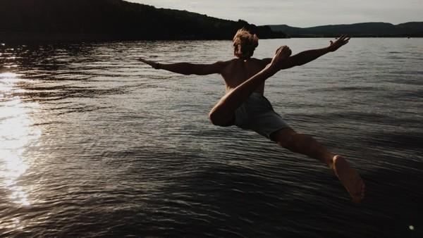 Ein Mann springt in einen See