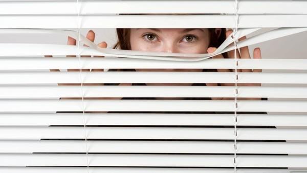 Eine Frau schaut durch einen Schlitz einer Schalousie