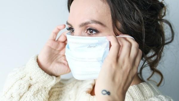 Die Frau zieht sich ihre OP-Maske auf