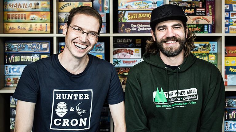 Zwei Männer stehen vor einem Regal mit Brettspielen und lachen in die Kamera.