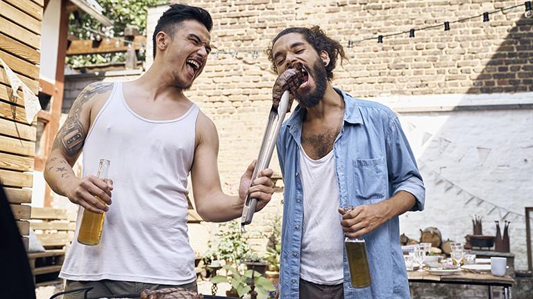 Zwei Männer stehen an einem Grill und halten jeweils ein Bier in der Hand. Der eine füttert den anderen mit einem Steak.
