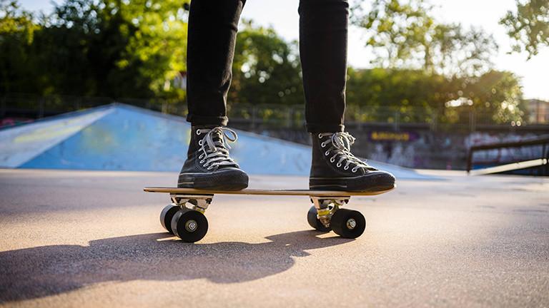 Zwei Füße stehen auf einem Skateboard, im Hintergrund ist eine blaue Halfpipe.