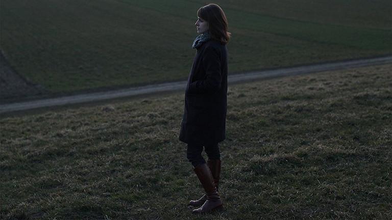 Eine Frau steht im Profil auf einem Feld.