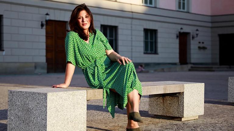 Eine Frau sitzt mit überschlagenen Beinen und in einem grünen Kleid auf einer Bank.
