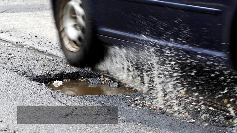 Ein Schlagloch in einer Straße. Ein Auto fährt daran vorbei.