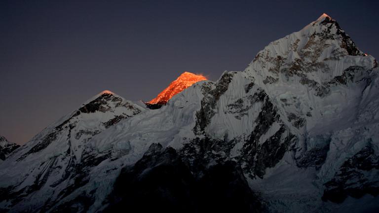Ein Blick ins Himalaygebirge mit einem rötlich angeleuchteten Gipfel.