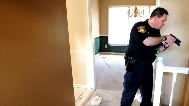 Ein Polizist hält in einem Haus, das gerade zwangsgeräumt wird, eine Waffe in seinen Händen und sucht nach Hausbewohnern.