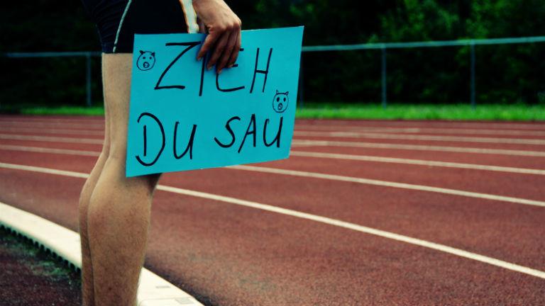 """Ein Läufer hält ein Schild, auf dem """"Zieh, du Sau"""" steht."""