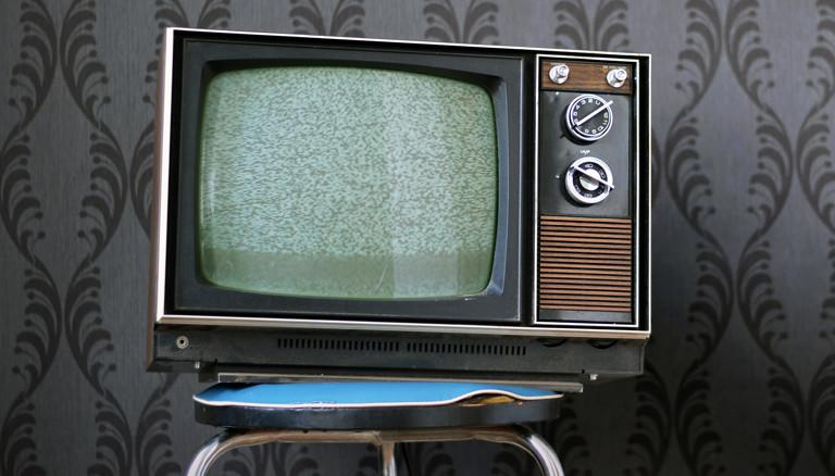 Fernseher vor altmodischer Tapete.