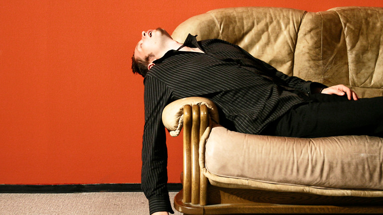 Ein Mann liegt auf einem Ledersofa und schläft oder ist faul.