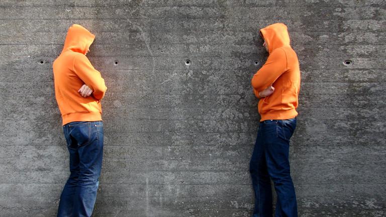 Zwei Männer stehen an einer Wand.