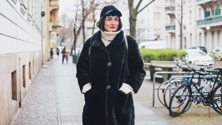 Eine Frau steht mit Händen in den Manteltaschen auf dem Bürgersteig.