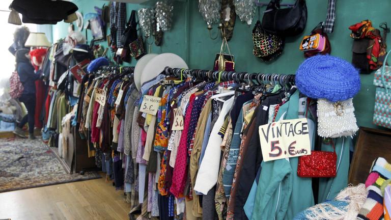 """Ein Laden, in dem an einer Stange an der Wand viele Klamotten hängen. Auf einem Schild steht """"Vintage 5 Euro""""."""