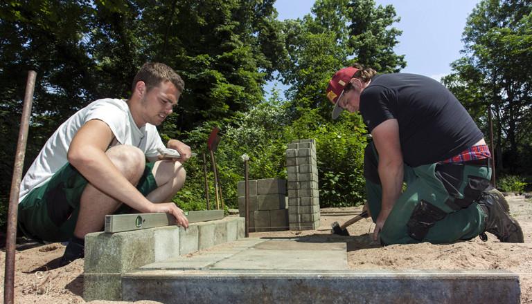 Zwei junge Azubis arbeiten auf dem Bau