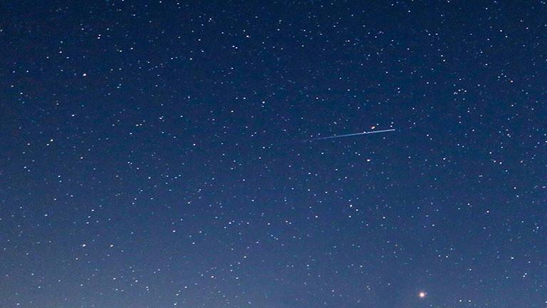 Eine Sternschnuppe am Sternenhimmel.