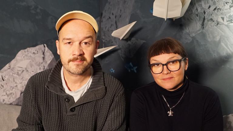 Ein Mann und eine Frau sitzen nebeneinander und schauen in die Kamera.