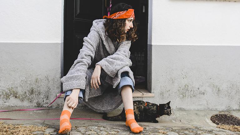Ein Mädchen sitzt in einem Hauseingang und schaut nach rechts. An ihren Füßen sitzt eine Katze.
