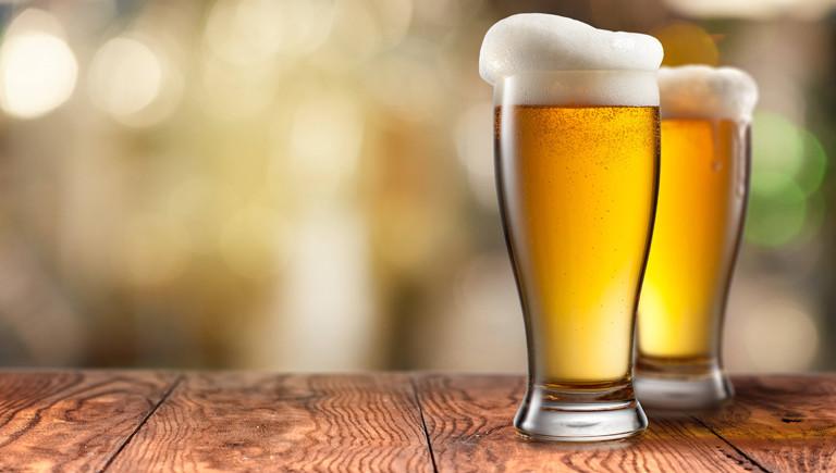 Zwei Biergläser stehen auf einem Holztisch.