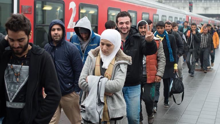 Geflüchtete gehen am 29.10.2015 nach ihrer Ankunft mit einem Sonderzug aus Österreich auf dem Hauptbahnhof in Passau (Bayern) auf einem Bahnsteig entlang.