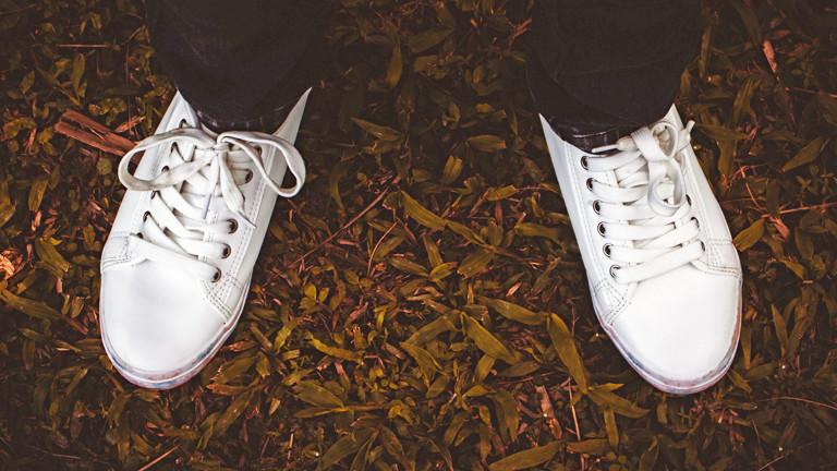 Zwei weiße Sneaker-Schuhe auf Laub und kleinen Ästen.
