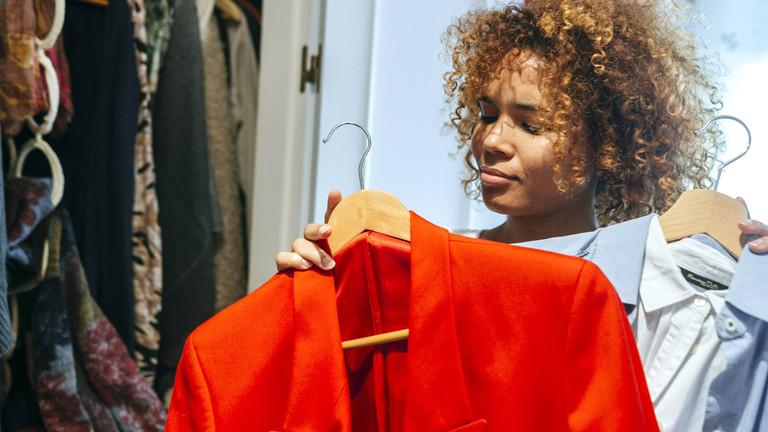 Eine Frau betrachtet Klamotten aus ihrem Kleiderschrank.