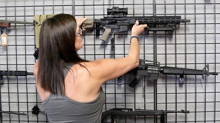 Eine Waffenhändlerin präsentiert ein Sturmgewehr.