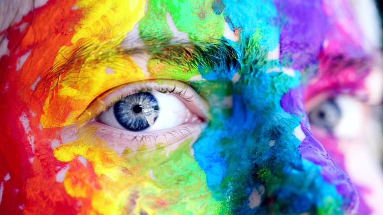 Eine Person ist in Regenbogenfarben angemalt.