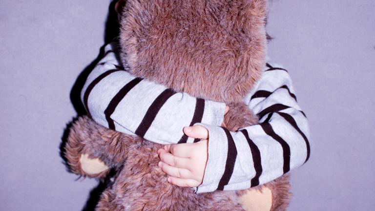 Ein Kind, das seinen Teddybären fest umarmt. Weil der teddy so groß ist, sind vom Kind nur die Arme zu sehen.