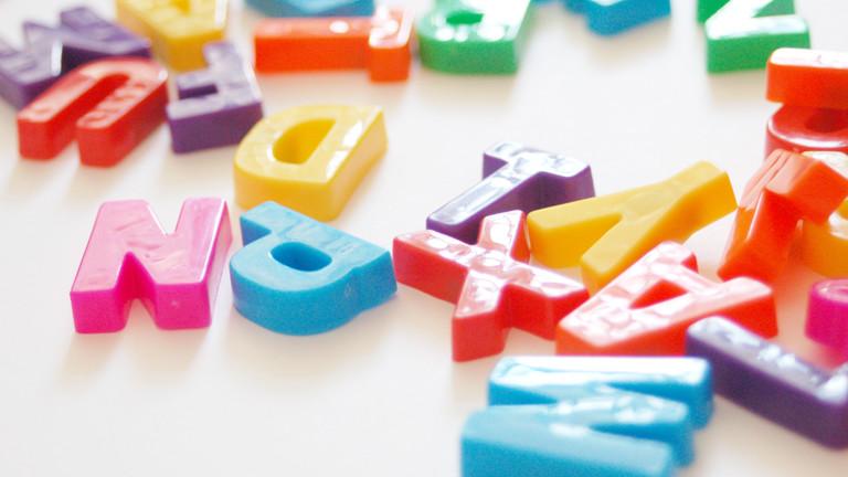 Bunter Buchstabensalat aus Plastikbuchstaben