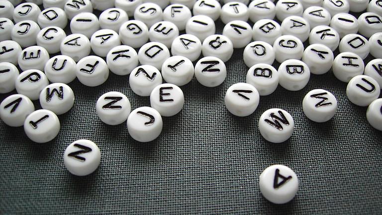 Weiße Spielsteine mit schwarzen Buchstaben liegen auf einem schwarzen Untergrund