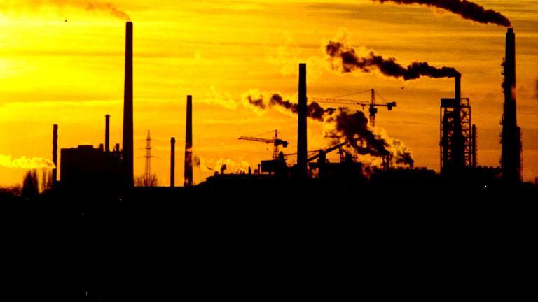 Eine Industrielandschaft mit rauchenden Schornsteinen in der Abendsonne.