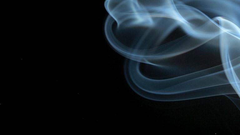 Zigarettenrauch vor schwarzem Hintergrund